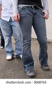 Stock image of youths wearing jeans in an urban setting.