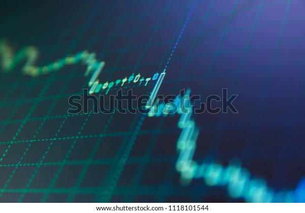 Stock market graph on the screen. Investing and concept gain and profits with faded candlestick charts. Candle stick graph chart. Stock market chart, graph on blue background.