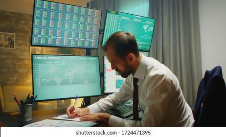 Stock market trader pointing at monitor computer and taking notes. Financial crash.