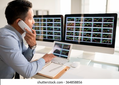 Stock market trader talking on telephone when looking at the monitor