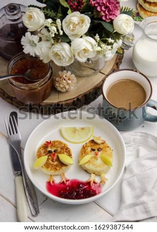 идея интересного завтрака для ребенка. цыплята сделанные из сырников и фруктов на светлом фоне.  Сток-фото ©