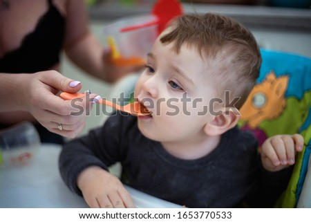 Мама кормит малыша. Кормить ребенка с ложечки.  Сток-фото ©