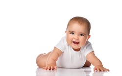 a baby in a white bodysuit lies on her stomach on the floor with her arms outstretched and tries to crawl. Happy infancy and childhood concept