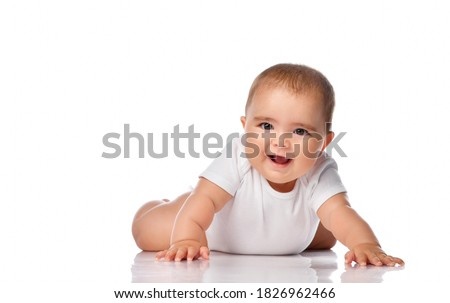 a baby in a white bodysuit lies on her stomach on the floor with her arms outstretched and tries to crawl. Happy infancy and childhood concept Stock photo ©