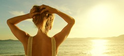 A back side view on a wonderful young woman watching to sea and raising her hands on sunrise