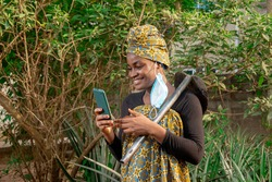 A beautiful African female farmer with nose mask, checking her smartphone with a hoe hanging from her shoulder in her pineapple farm