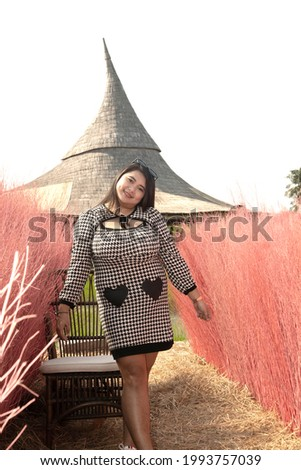 A beautiful Asian fat female poses standing with pink dry trees in the background in the public park. Stock photo ©