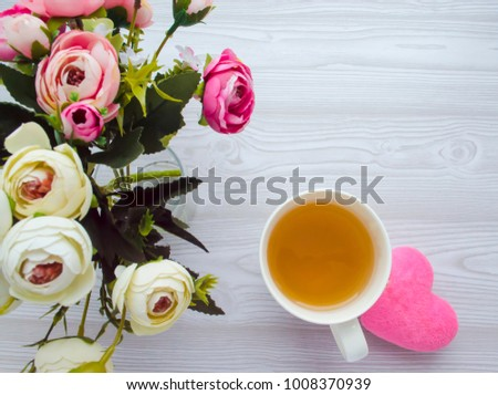 a beautiful bouquet of small pink and white roses, a cup of tea, a plush heart on a simple wooden background. view from above #1008370939