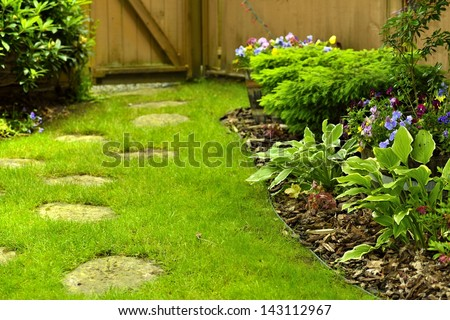 A beautifully landscaped back yard with stepping stones.
