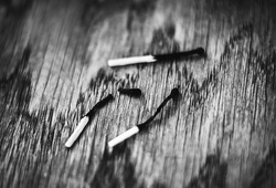 A black-and-white image of three burnt matches lying on a wooden table. One of the matches burned out and broke. Danger.