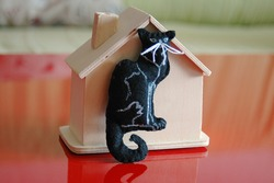A black cat next to a wooden house on a red background