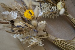 A bouquet of dried flowers in natural, white, lilac, yellow tones. Contains: lavender, ears of wheat, gelichrizum, ruscus on a beige background