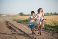 A boy and a girl ride a bicycle in the summer field