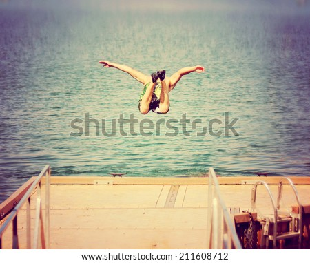 a boy jumping of an old dock...