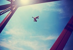 a boy jumping off an old train trestle bridge into a river done with a retro vintage instagram filter (SHALLOW DOF)