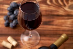 A bunch of ripe blue grapes with a glass of red wine with wine corks nearby, and a sealed bottle of red wine on a textured wooden background. Winemaking, wine tasting