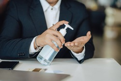 A business person is spraying alcohol on his hands Before starting work to prevent the spread of the corona virus or COVID19.