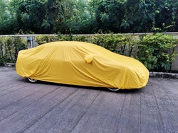 A car with a protect covered.  Yellow sheet on the pavement.