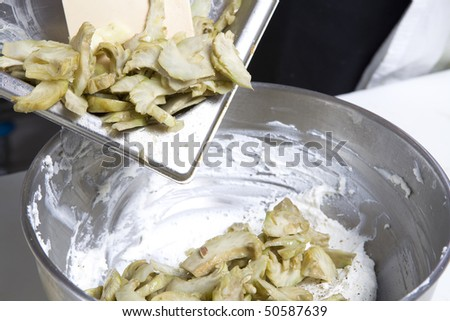 A chef working in a kitchen - cut artichoke and going to fry griddle