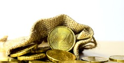 A closeup, main, a twenty cent euro coin, in a cloth bag with more coins scattered on the table, white background.