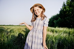 A country girl in a straw hat and a vintage dress is standing in a field with green rye. Smiles