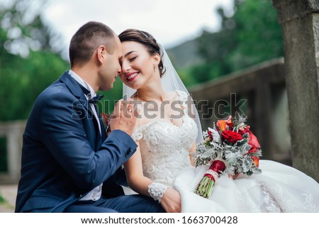 A couple of newlyweds posing on the stairs. Happy Newlywed woman and man embracing and kissing. groom with boutonniere. Beautiful wedding bouquet. Wedding day. Sincere emotions Foto stock ©