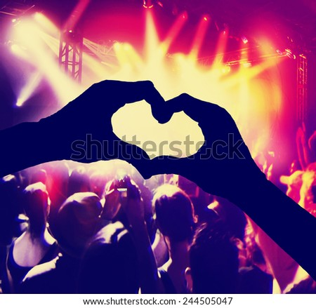 a crowd of people at a concert with heart shaped hands over the stage toned with a retro vintage instagram filter
