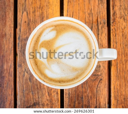 A cup of coffee with leaf pattern in a white cup on wooden background