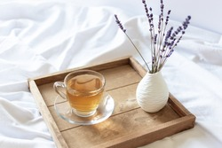 A cup of tea in the morning on wooden tray in bed. Romantic morning tea drink.