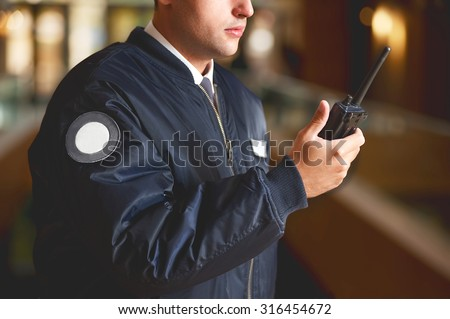 a cut face close up in a security guard with a portable wireless transceiver on a blurry background