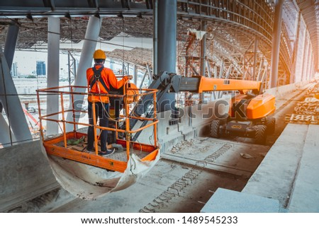 A Engineer wearing safety uniform and safety helmet ,controlling straight Boom Lift to construction roof on sky rail train platform station .