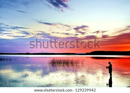 A fisherman with rod on a lakeside at sunset