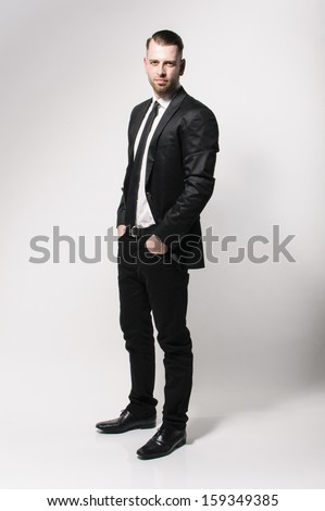 A full length portrait of an young man with short hair and stubble wears a dark suit and a narrow tie. He looks cool in the camera and has his hands in his pockets. - stock photo
