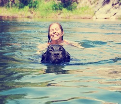 a girl and a big lab dog swimming in the water toned with a retro vintage instagram filter effect app or action