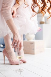 a girl in a pink skirt and pink shoes on her heel raises a glass of wine.  Red-haired girl stretches for a glass of champagne at a party