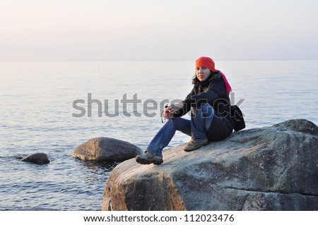 a girl sitting on stones at sunset beach