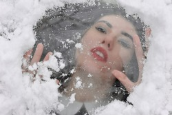 A girl under the ice and snow screams for help.An interesting idea for a fabulous winter photo shoot. A woman with dark hair, brown eyes and fair skin of Ukrainian nationality.