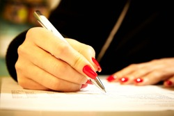 A girl with beautiful red nails fills a document with a ballpoint pen. Female hand holds a ballpoint pen.