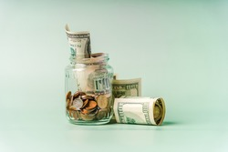 A glass jar with different coins on a pastel background with space for text. The concept of accumulating savings