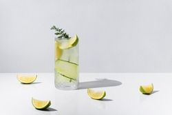 A glass of detox drink, water with fruit and ice. Contains cucumber, lime wedges and green leaves on a white table, with hard shadow. Summer concept, tropical and cool cocktail