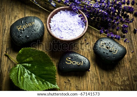 a green leaf, healing stones, a bowl with lavender herb salt and dry French lavender in old style like a concept for wellness of spirit, soul and body - stock photo