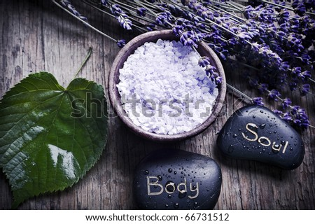 a green leaf with healing stones, a bowl with lavender herb salt and dry French lavender in old style like a concept for care and wellness about spirit, soul and body