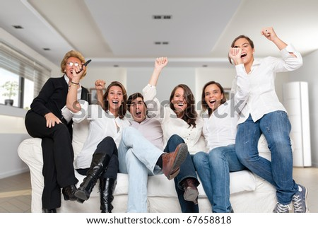 A group of family members sitting at home cheering