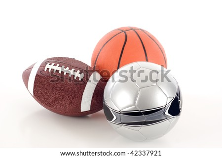 A Group of Sports Balls - an American Football, Soccer Ball, and Basketball - Isolated over a white background