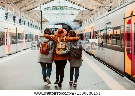 A group of young friends waiting relaxed and carefree at the station in Porto, Portugal before catching a train. Travel photography. Lifestyle.