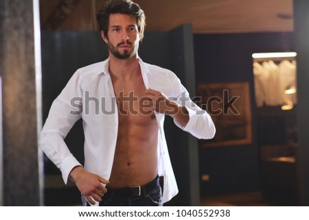 A handsome man in his loft dresses his sexy white shirt , looks into his room and smiles with a sure look at himself. Concept of: elegance, business, work #1040552938