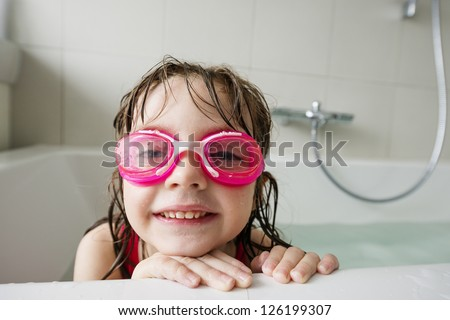 a happy  little girl with swim glasses bathing