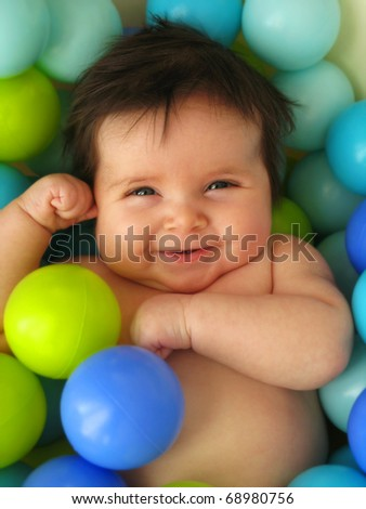 A happy 3 months old baby in a bath of balls.