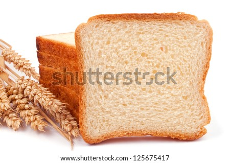 A heap of bread slices and one slice like a copy space, leaning on the heap and wheat ears - isolated on white