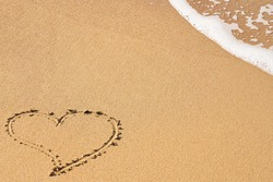 A heart symbol written on a sandy beach with foam and water background. Valentines day concept.
